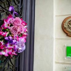 purple-flowers-wreath-on-the-front-door-of-wedding-venue-prague